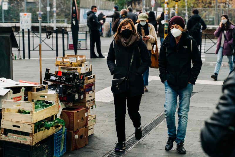 Couple walking at a farmer's market wearing masks.