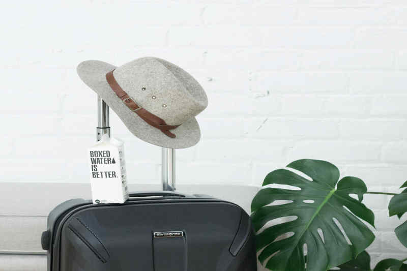 Suitcase, hat, and boxed water.
