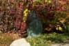 An oxidizedc copper cat statue hidding in a garden