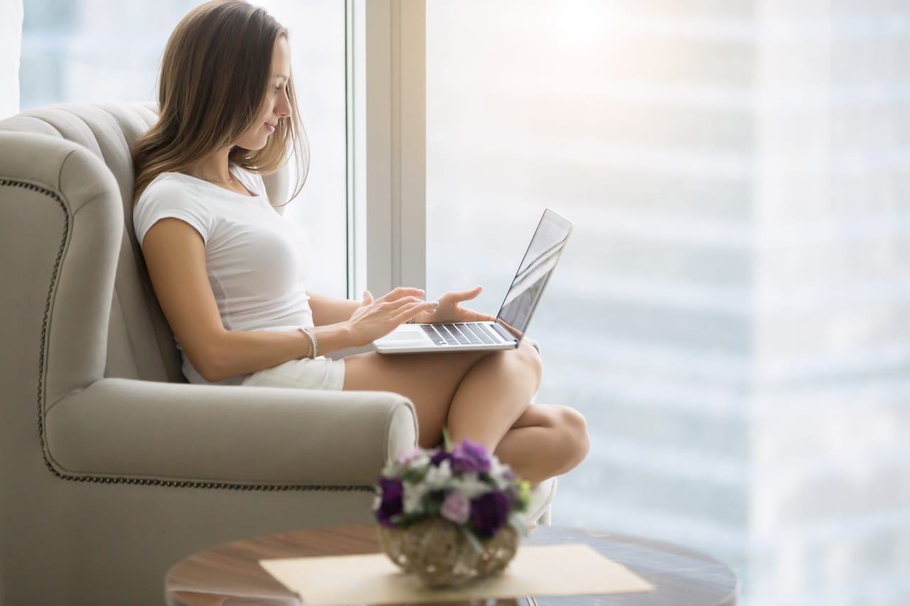 Young woman in a modern room, comfortable in her armchair with a laptop, operating her business, setting up business on the Internet, seeking for potential customers, SEO consultant. Lifestyle