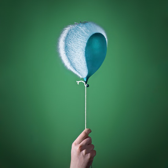 Photo of a water balloon bursting; it is attached to a string like a helium balloon.