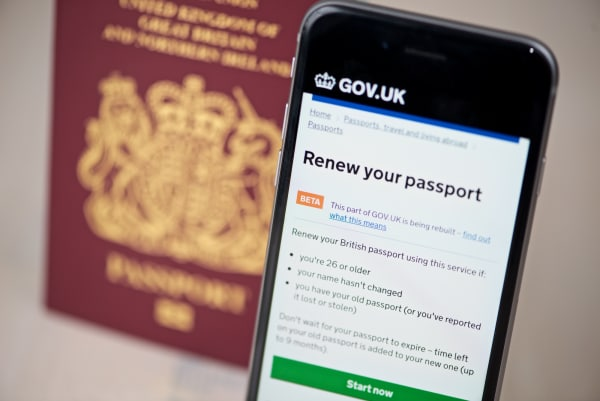 Photo of the passport renewal service on a phone, in front of a UK passport.