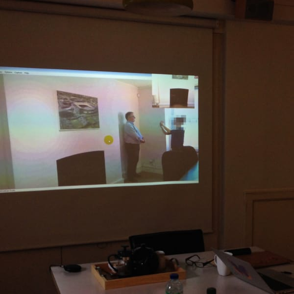 A photo from a user research session. A user is attempting to take a passport-style photograph.