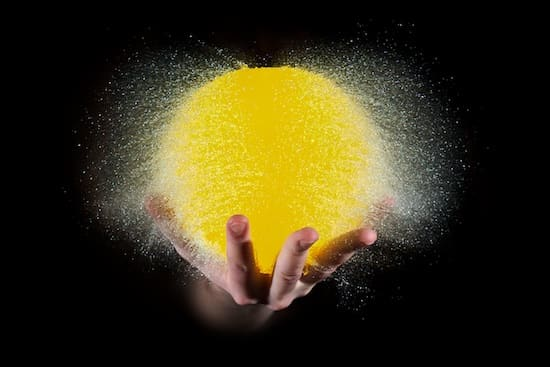 Photo of a water balloon bursting. The balloon is resting on a hand, and lit up like the sun.