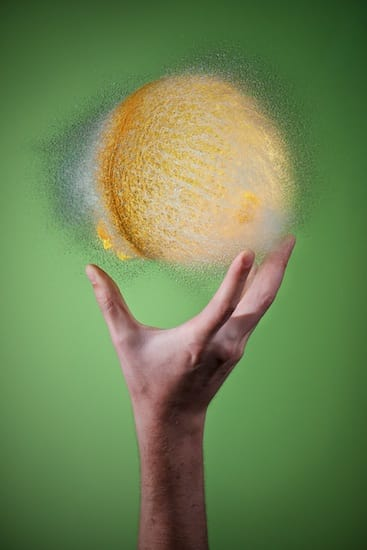 Photo of a burst water balloon. It's light yellow, and held in a hand.