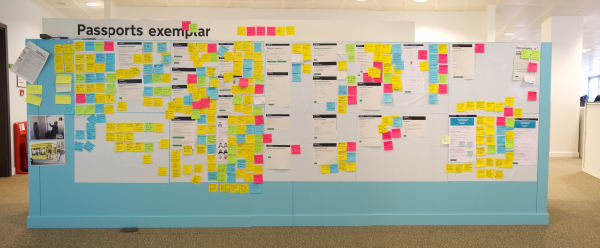 Photo of the project's design wall. Screenshots of the service are printed out and stuck on the wall, with annotated post-its on top.