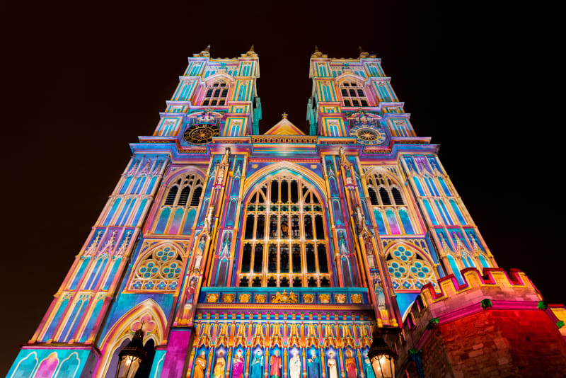 A photo of the front of Westminster Abbey at night. The entire front is lit up in bright pastel colours.