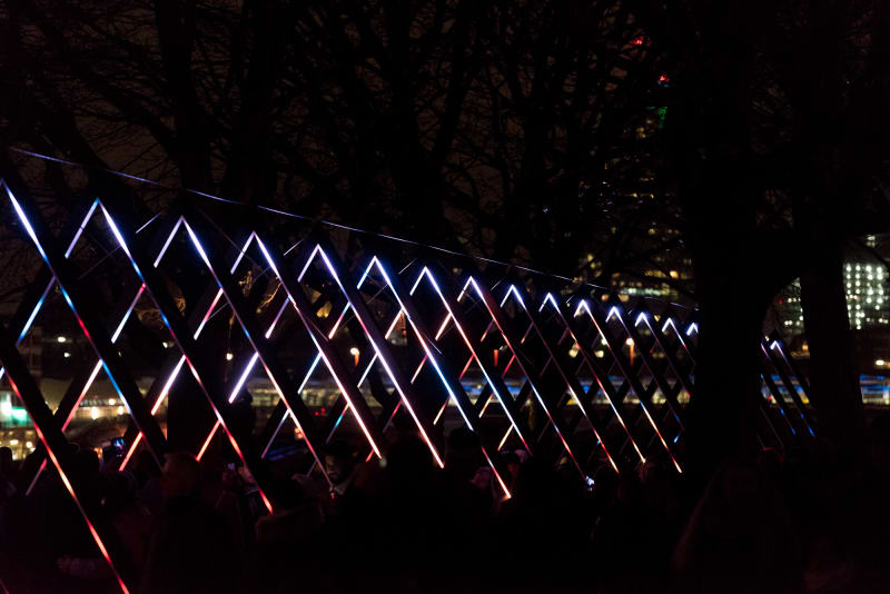 A photo of a light triangular light sculpture. A series of triangles is each lit up in white and bright colours. The triangles recede in to the distance.