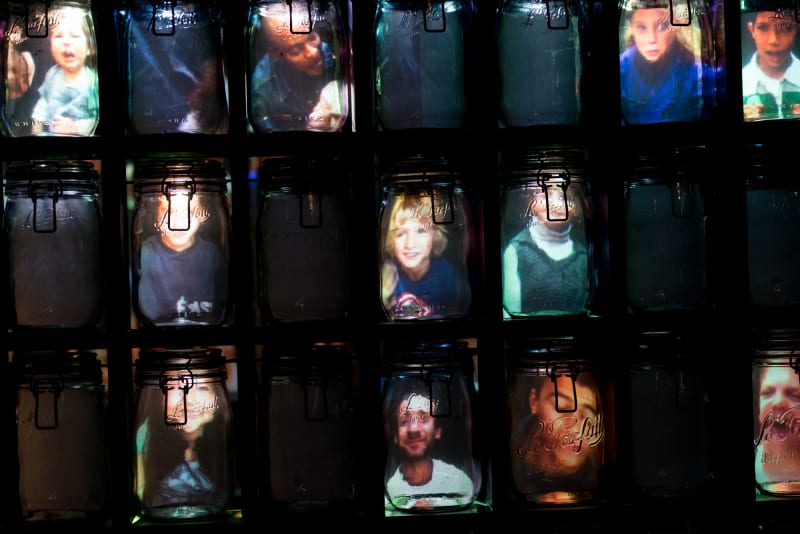 Faces appear lit up inside three rows of Kilner jars.