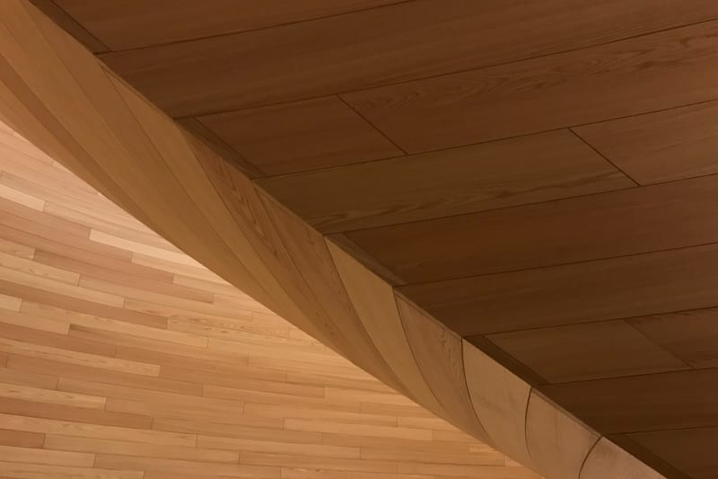 A detail of a curved wooden wall. The panels have a regular pattern.