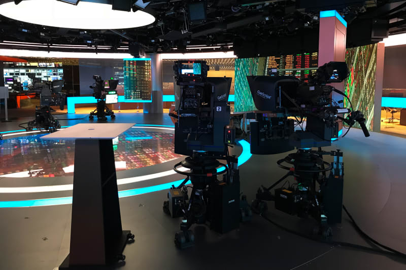 The Bloomberg TV studio. There are several large cameras pointed at a desk, and several large LED displays.