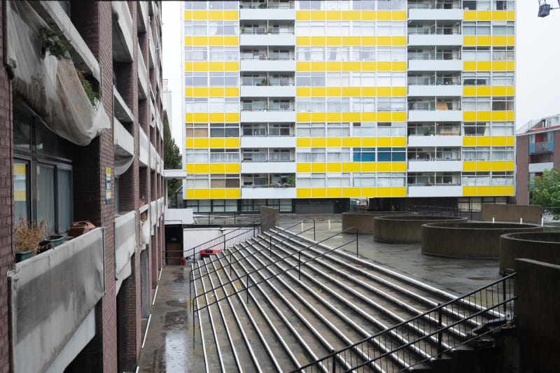 A photo looking down the edge of a tower block with a tower block with yellow trim in the background.
