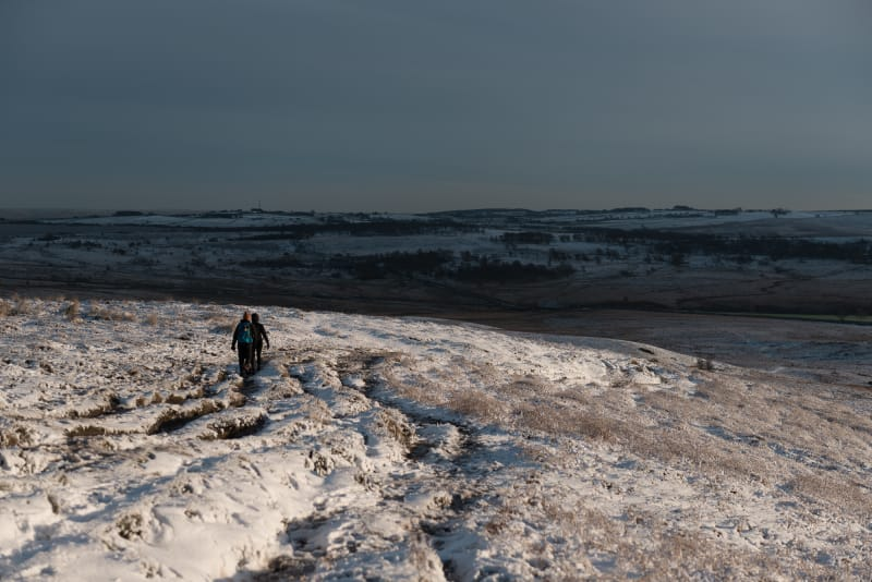 A pair of walkers decend a snow covered hill.