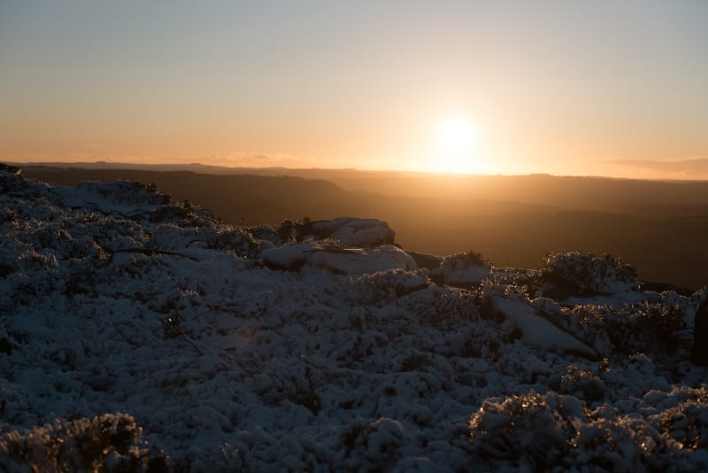 A golden sunset with snow covered rocks and grasses in the foreground.