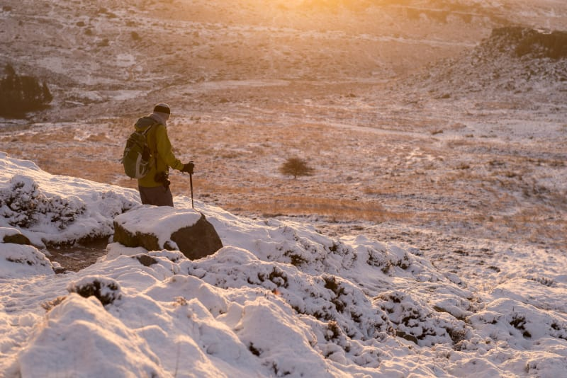 A hiker with hiking pole descends a snow covered hill at sunset.