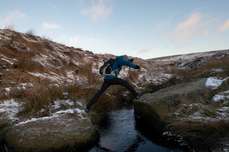 Ed Horsford mid leap whilst crossing a small stream.