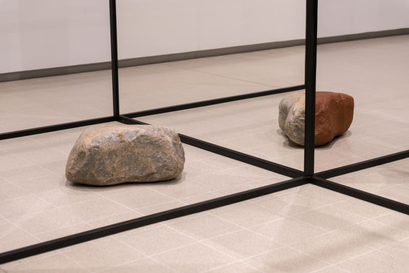 A photo of a sculptural form in a room. There are black struts in a grid shape with two large rocks on the ground.
