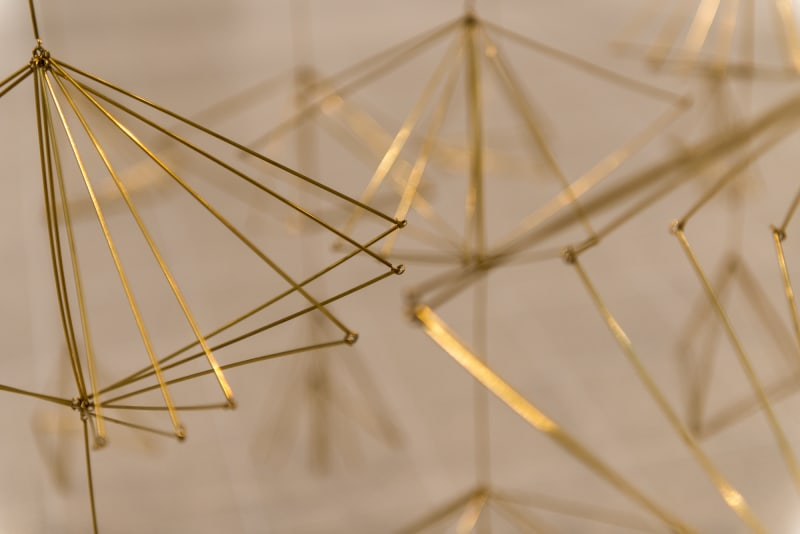 A closeup of a sculpture made from gold-coloured wires bent in to angled shapes.