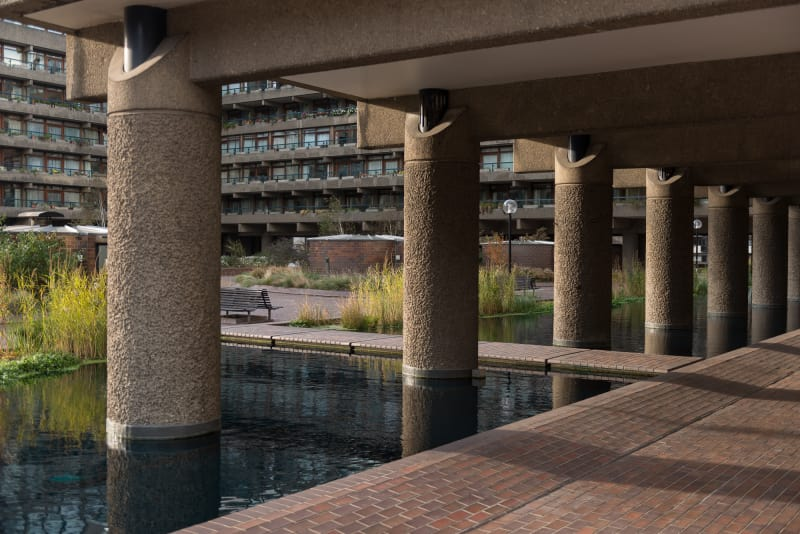 A photo of a Barbican walkway with a pond in the foreground.