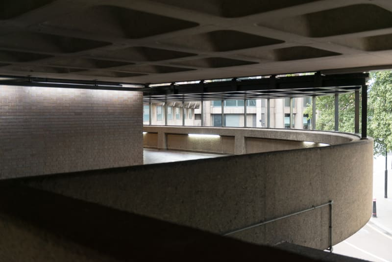 The side of a curved covered walkway in the Barbican.