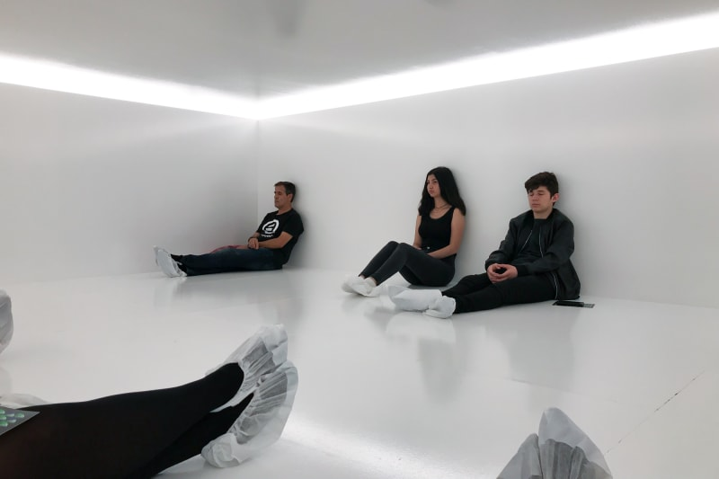 Several people with paper socks are sat in a gloss white room with white light overhead.