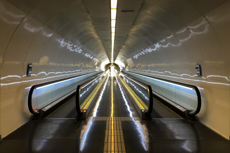 A photo looking down a long corridor with two moving walkways on either side.