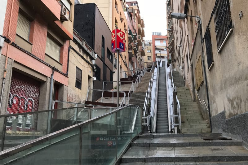 A photo looking up a steep street / alley in Barcelona. There's an open-air escalator in the middle and steps either side.