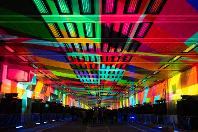 A photo looking straight down the covered Beech Street. The entire ceiling is covered with a patchwork of bright projected colours.
