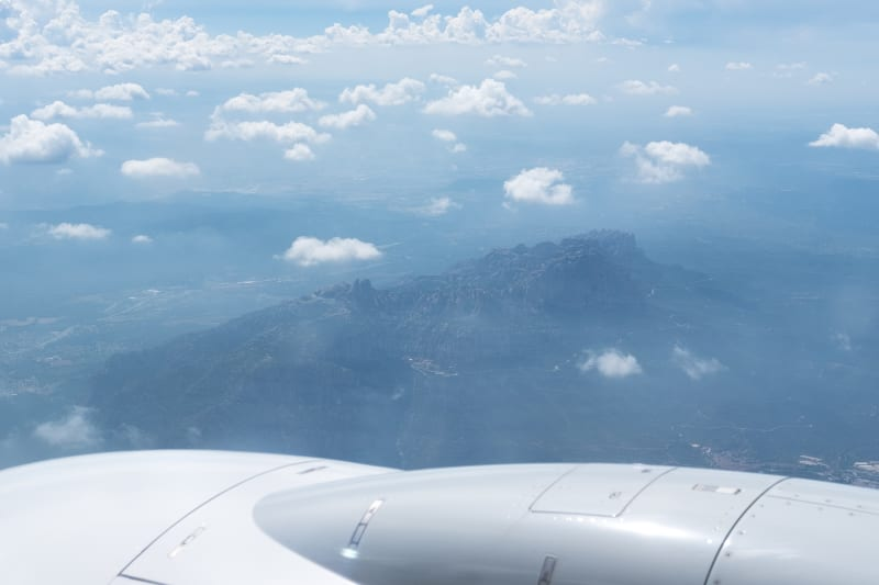 A photo of the Montserrat mountain range taken from an airplane. A plane engine is visible in the foreground.