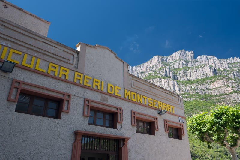 """The front of the lower Montserrat cable car station. It has bright yellow letters on the side, reading """"Funicular aeri de Montserrat""""."""