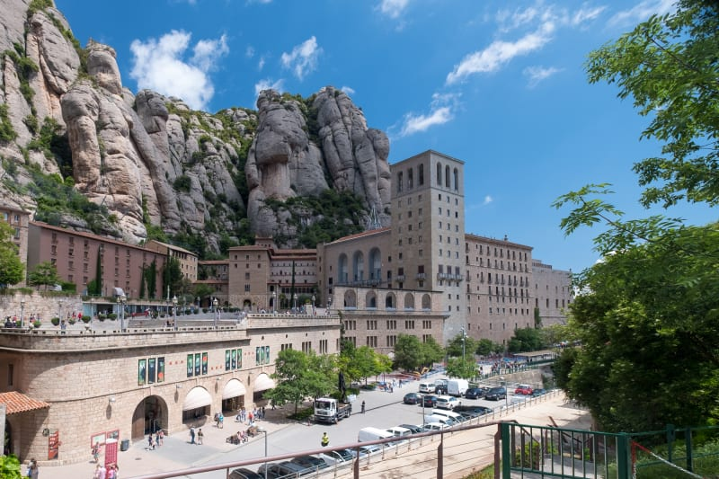 A view of the town of Montserrat. The cathedral is in the foreground, with mountains looming behind.