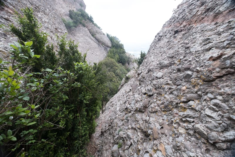 A view down a cut v in two rock faces. Both faces are very steep.
