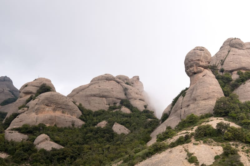 Looking up at the peaks of some mountains in Montserrat. The rocks are bulbous and separated like molten lumps.