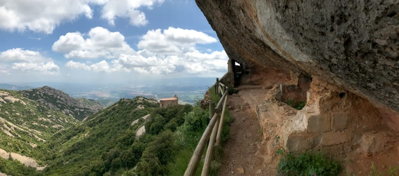 A panorama half looking over the Montserrat countryside and half looking at a path along the side of a mountain that is covered by steep rock.