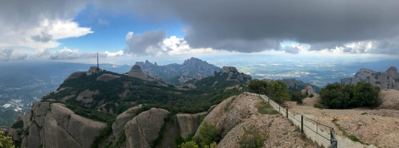 A panorama taken a the top of Sant Jeroni in Montserrat. The sky is gloomy but clear skies can be seen in the distance.