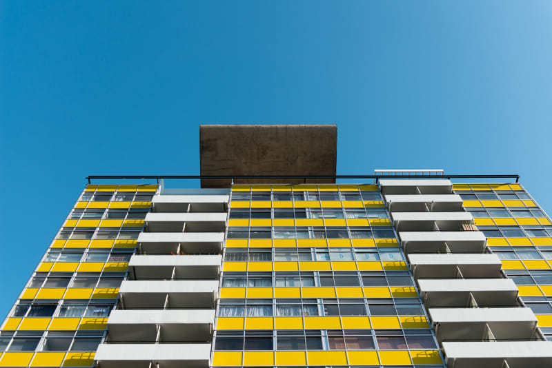 Looking up at the top of a tower block on the Golden Lane estate. The block has contrasting patches of bright white and yellow.