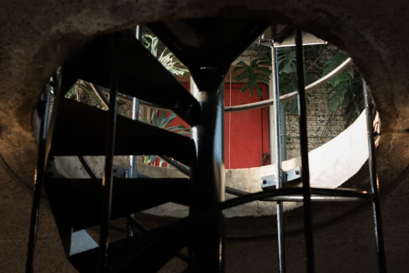 Looking up a spiral staircase at the level above. There's a red door in the distance.