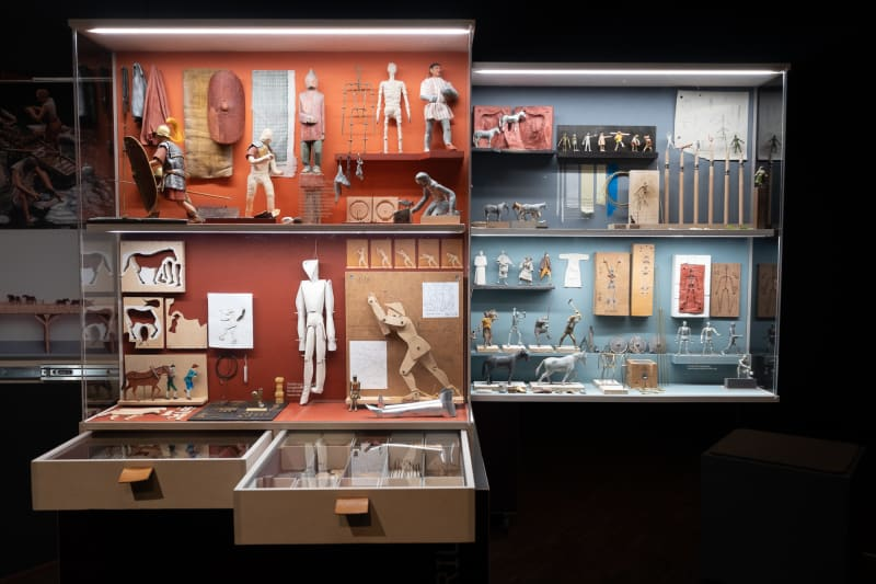 A photo of a display case showing many small models of people and various tools. The models are for use in historical dioramas.