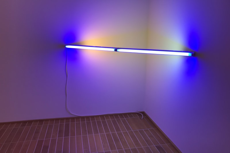 Photo of a light sculpture by Dan Flavin in the Kunstmuseum. The sculpture is a long fluorescent bulb stretching between two walls in the corner of a room. The bulb is the only source of light, and gives of a blue and white light.