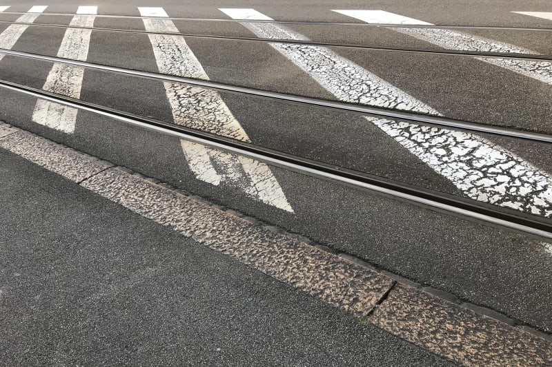 A photo of tram tracks and painted white stripes on a stretch of road.