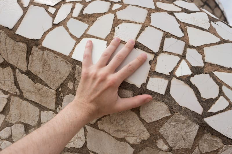 A hand rests on a large mosaic of broken white tiles.