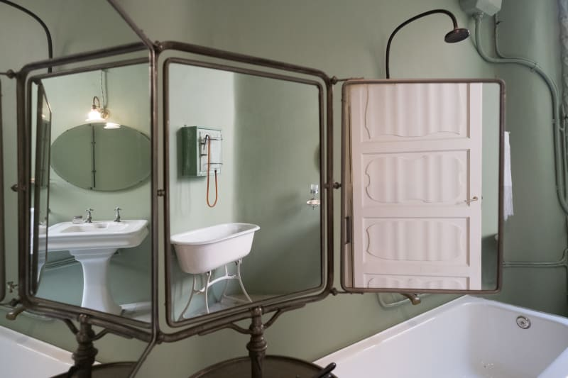 A photo of a 3-part folding mirror in a bathroom. Reflected in the mirrors are a sink, a bath, and a doorway.