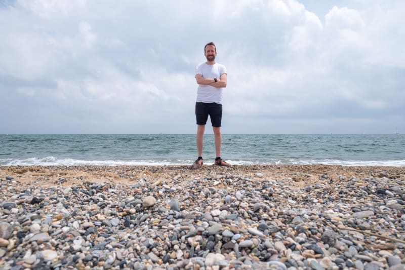 A photo of Ed Horsford on a beach. The camera is positioned low down, pointing directly at the water. Ed is in the centre, facing the camera with arms folded.