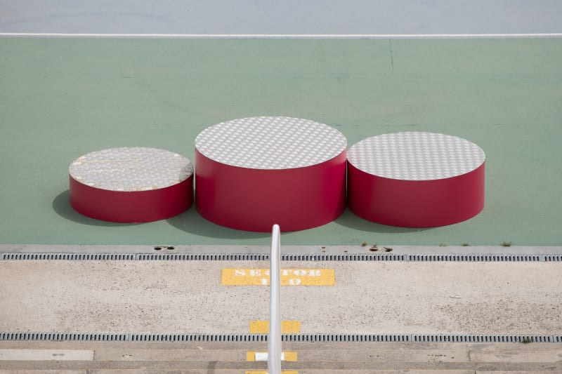 A photo of the winners podium at the Barcelona olympic stadium. The podium is made of three red cylinders of different heights.