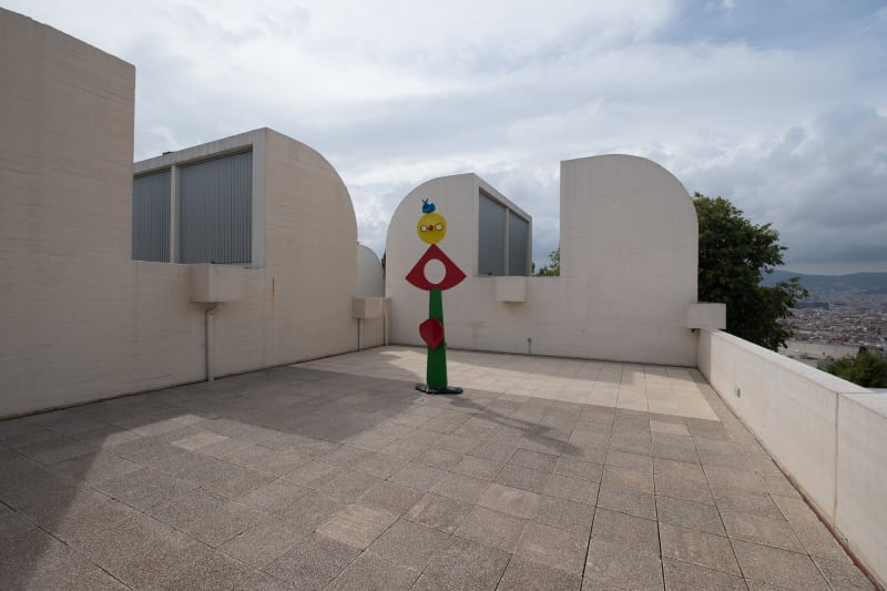 A photo taken on the roof of the Joan Miró Foundation. There are white walls on the side, some with rounded corners. There's an abstract coloured sculpture in the centre of the terrace.