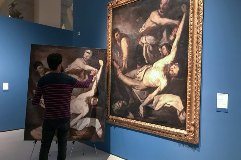 An artist painting a replica of a large oil painting hung on the wall.