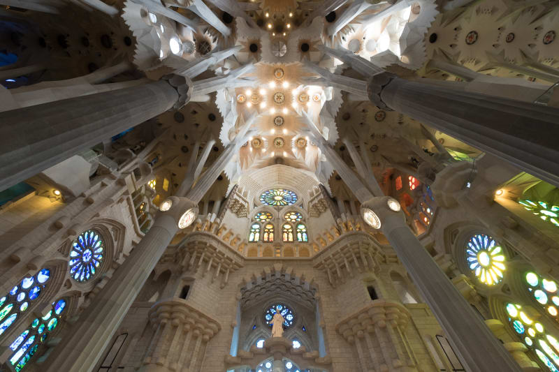 Looking towards the ceiling of the main atrium of la Sagrada Família. The very top of the ceiling is especially bright from many small lights.