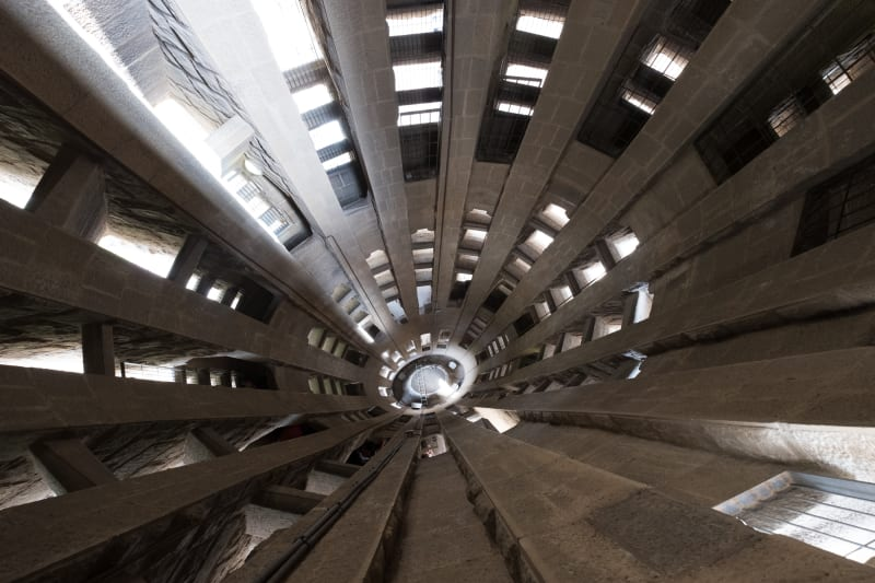A wide angle photo looking down void of the interior of one of a la Sagrada Família tower.