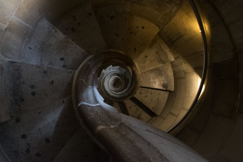 Looking directly down a tight stone spiral staircase