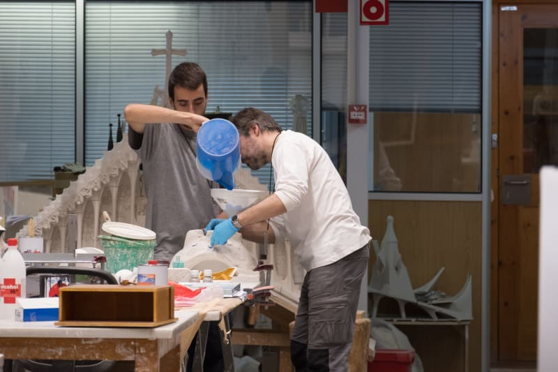 Two model makers pour plaster in to a mould.